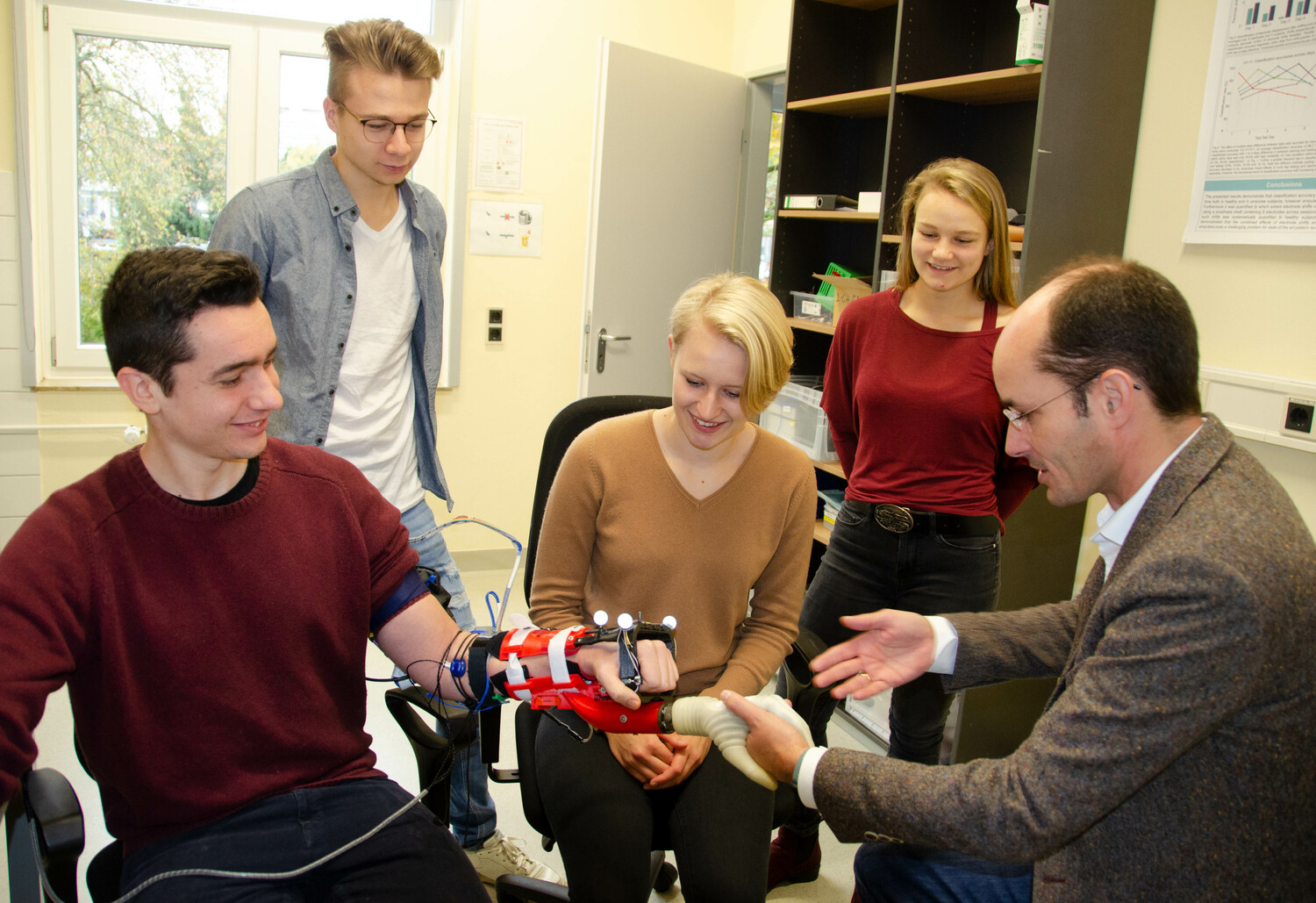 Professor Arndt Schilling from ART-Lab (right) presents the intuitive operation of a hand prosthesis to students of medical engineering at the Gesundheitscampus Göttingen.