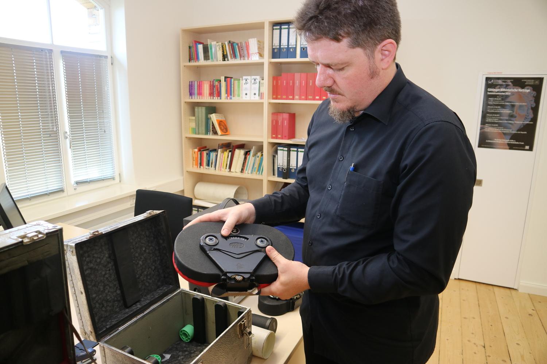 Kustos Dr. Martin Lindner mit dem Magazin einer Arriflex-16mm-Filmkamera