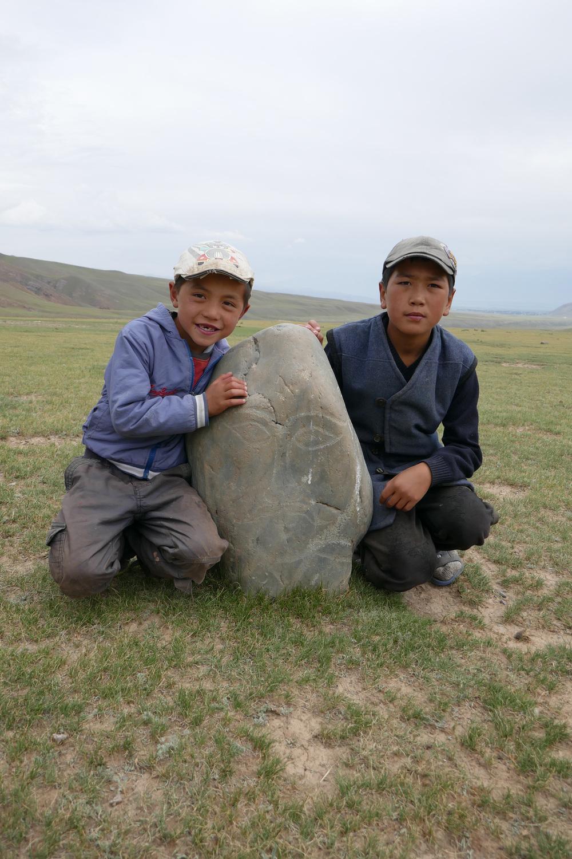 Zwei kirgisische Jungen zeigen einen Balbal, eine Steinfigur mit menschlichen Formen.