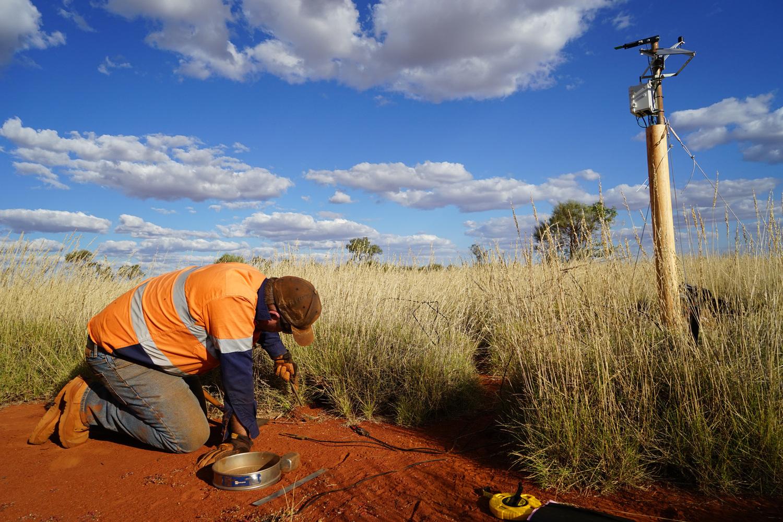 Dr. Todd Erickson von der University of Western Australia bei der Installation von Bodenfeuchtesensoren, die im Inneren eines Feenkreises und unter umgebenden Triodia-Gräsern vergraben wurden. Auf der rechten Seite befindet sich die solarbetriebene Wetterstation, die die Daten im Sommer und Winter automatisch aufzeichnete.
