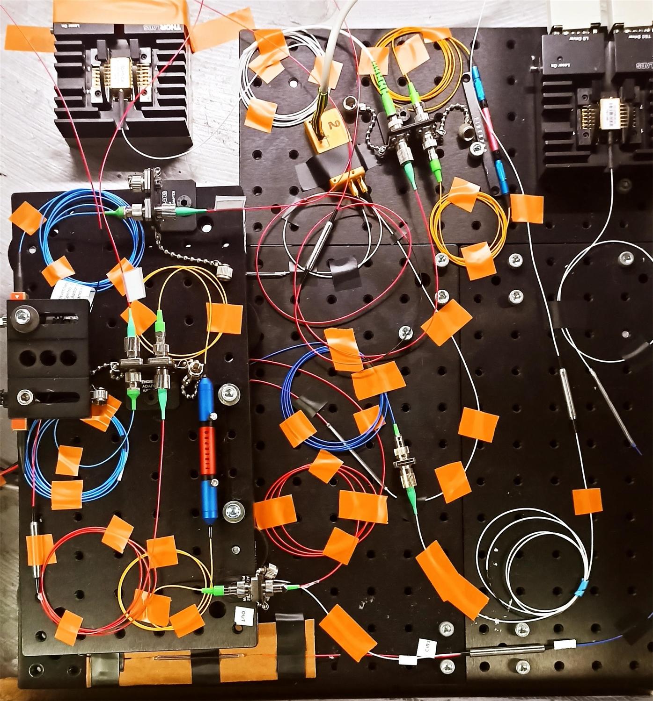 Experimenteller Aufbau der dendritischen Komponenten von ADOPD bestehen aus Lichtleiterstrecken (aufgerollt), Verbindern (silbern) und optischen Rechenkomponenten (farbig, bzw. schwarz).