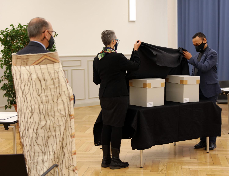Hinemoana Baker und Te Arikirangi Mamaku von der maorischen Delegation nehmen das schwarze Tuch ab, mit dem die tūpuna (Ahnen) während der Zeremonie bedeckt waren.