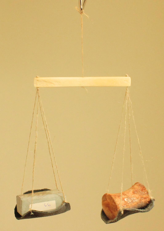 Die Art von Waage, die eine bronzezeitliche Händlerin mit sich führte, wenn sie von einem Markt zum anderen zog, um Handel zu treiben: aufgehängte, nachgebildete Knochenwaage mit Flachsschnüren und Lederbeutel, die zwei nachgebildete Gewichte im Gleichgewicht hält.
